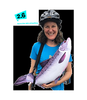 Woman in cycling gear holding stuffed Salmon